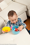 9 month old baby boy finding toy hidden inside plastic pot