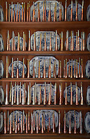 Rows of copper bugels line the shelves of a dresser displaying blue and white crockery