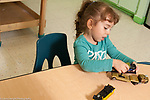 Education Preschool 3-4 year olds girl playing with toy vehicles talking to herself
