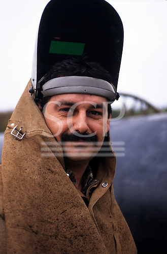 Slovakia. Gas pipeline worker in protective leather welding visor.