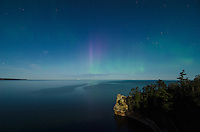 A bright full moon illuminating Miners Castle with the Northern Lights over Lake Superior. Pictured Rocks National Lakeshore, Munising, MI