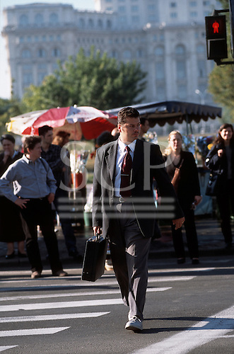 Bucharest, Romania. Businessman in jacket and tie carrying briefcase; Palace of Culture (formerly Ceaucescu's Palace).