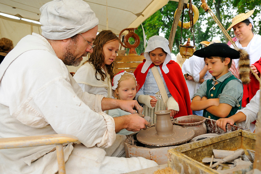 Families often followed soldiers to prepare food and nurse the wounded. Colonial potter attracts crowd of children of Continental Army and militia units at a Revolutionary War encampment, Fort Ticonderoga, New York, USA.