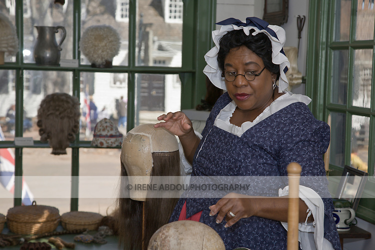 A woman makes a wig in the Barber & Peruke Maker Shop at Colonial Williamsburg, Virginia.