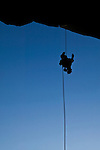 A rock climber rappels from the cliff.