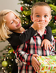 Sister (6-7) covering mouth of brother (6-7) with hand during Christmas celebration