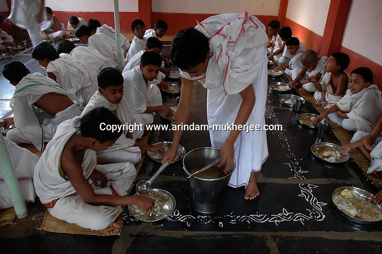 Students of Om Shantidhama having their vegeterian simple lunch. Om Shantidhama is a residential vedic school for boys. Nestled among the confluence of hills, forest and rivers - Om Shanti Dhama is a world removed from the maddeningly fast and often chaotic urban India. Students from allover the country are selected to take part in its Vedic and free education system. What is unique about this institute is that they have blended the traditional and modern education system. Here computer and science is taught with the same passion as the Vedas and Shastras, helping the students to grow spiritually as well as earn a living. Bonding with the nature and animal world is a mandatory part of the institute's curriculum. Karnataka, India. Arindam Mukherjee