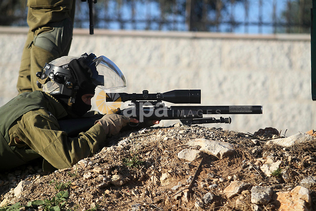 A member of the Israeli security forces aims his weapon at Palestinian stone throwers (unseen) during clashes in the West Bank village of Silwad, north of Ramallah, on March 21, 2014 following a protest of Palestinians against the expansion of the nearby Israeli settlement of Ofra. Photo by Issam Rimawi