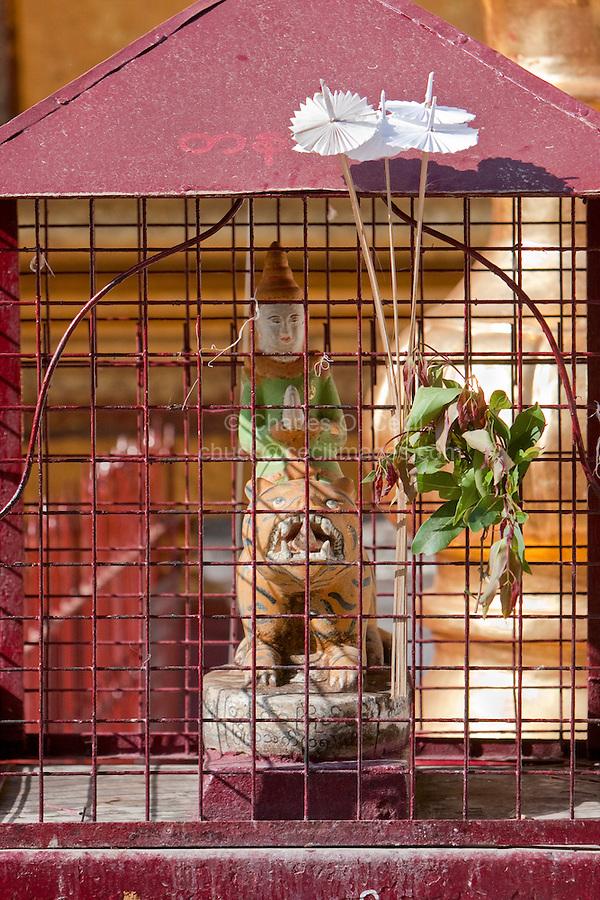 Myanmar, Burma.  Traditional Deity, a Nat, on a Tiger inside a Protective Screen.  Shwezigon (Shwezegon)  Pagoda, Nyaung Oo, near Bagan.