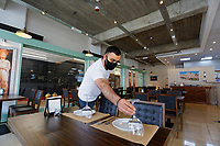 Pictured: Alexis Magdalidis, prepares tables before opening his Acropolis Greek restaurant in Swansea, Wales, UK. Monday 17 May 2021<br /> Re: Restrictions implemented by the Covid-19 Coronavirus pandemic, have been relaxed with hospitality business being allowed to open their indoors spaces in Wales, UK.