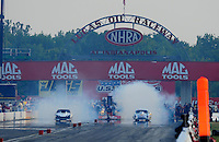 Sept. 3, 2011; Claremont, IN, USA: NHRA pro mod driver Melanie Troxel (right) does a burnout alongside teammate Leah Pruett during qualifying for the US Nationals at Lucas Oil Raceway. Mandatory Credit: Mark J. Rebilas-