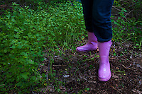 Pink rubber boots are worn for cleaning out invasive species undergrowth wild mustard garlic on Earth Day.