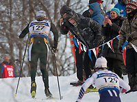 Spectators cheer as competirors in the Men's 30K Classic crest Gong Hill during the 2018 U.S. National Cross Country Ski Championships at Kincaid Park in Anchorage.