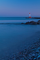 A view of the Oakville lighthouse from the stoney shore of Lake Ontario in the evening light.