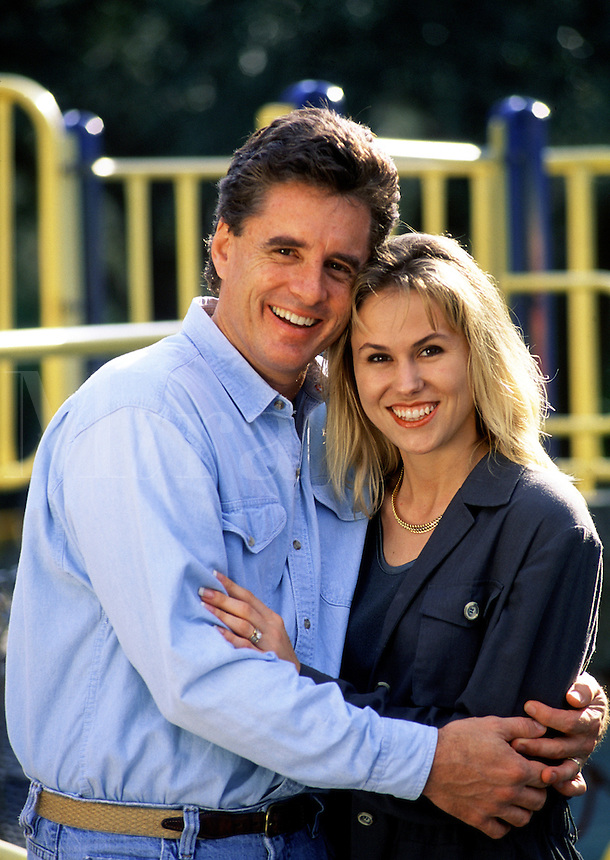 A smiling couple in an affectionate embrace on a playground.