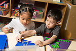 Preschool 4 year olds boy and girl playing with table toys boy helping girl to stretch rubber bands
