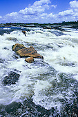 Iriri River, Amazon, Brazil. White water rapids in the river with blue sky and puffy white clouds.