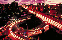 Traffic on a highway and its off ramp at twilight. Lights of cars forming streaks. Night shot. Skyscrapers and urban buildings lit up. Madrid, Spain.