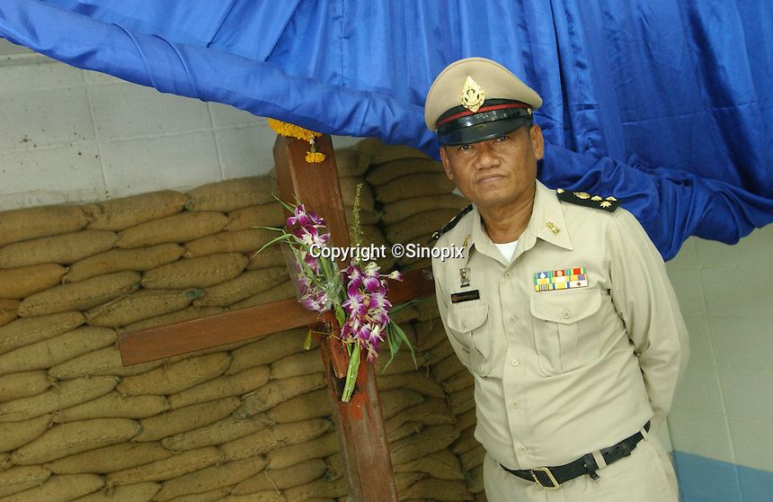 Thailand's only executioner Chawalate Jarubun of Bangkwang Central prison stands in front of the wooden execution cross where has has personally executed 55 prisoners.