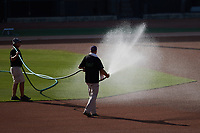 The Winston-Salem Dash grounds crew waters the infield prior to the game against the Hudson Valley Renegades at Truist Stadium on August 28, 2021 in Winston-Salem, North Carolina. (Brian Westerholt/Four Seam Images)