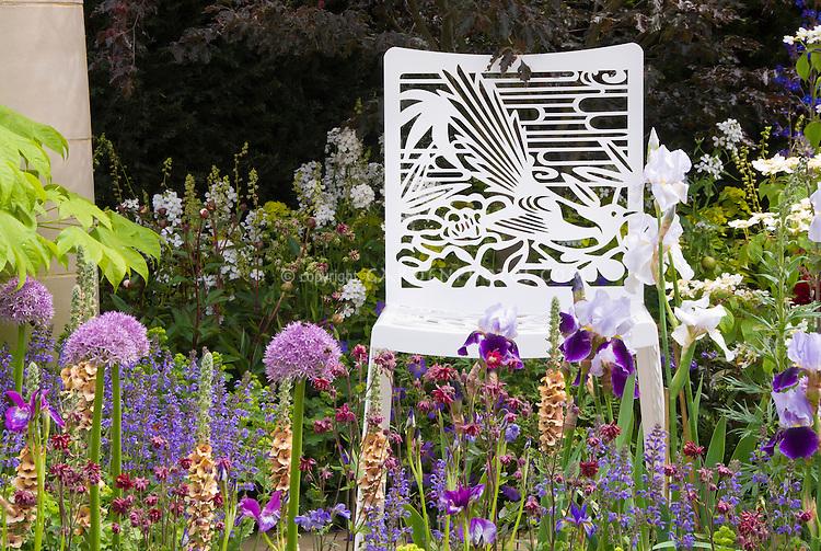 Garden Chair with Bird Ornamentation Detal in Flower garden in late spring, allium, Verbascum, Irises, salvia, spiky upright plants in romantic cottage garden style