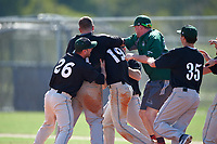 Plymouth State Panthers Luke Mancini (19) is mobbed by teammates, including Sean Engel (26) and Troy Micale (35), after a walk off victory during the first game of a doubleheader against the Edgewood Eagles on March 17, 2016 at Lee County Player Development Complex in Fort Myers, Florida.  Plymouth State defeated Edgewood 6-5.  (Mike Janes/Four Seam Images)
