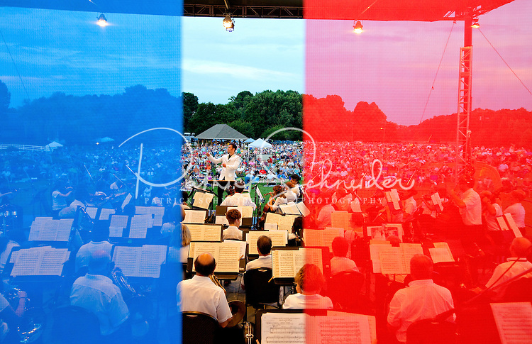 """Event photography of the Charlotte Symphony performing in a free outdoor concert June 17, 2012 at Duke Energy's McGuire Nuclear Station EnergyExplorium in Cornelius, NC. The symphony orchestra performed a """"musical travels"""" program. Jacomo Rafael Bairos conducted. Blue and red hues are intentional (photo taken through colored screens on stage)."""