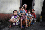 A mother sits with her four children in a poor area of Pokhara, Nepal.