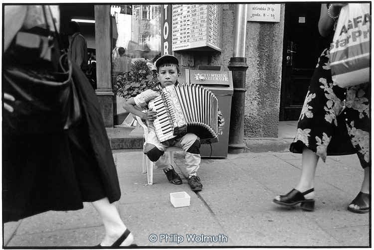 A young Roma boy collects money from tourists and local residents close to the main square in Krakow.  His ability on the accordion is limited: its purpose is to attract attention rather than entertain.