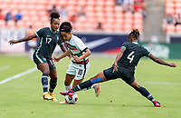HOUSTON, TX - JUNE 13: Jessica Silva #10 of Portugal is tackled by Glory Ogbunna #4 of Nigeria during a game between Nigeria and Portugal at BBVA Stadium on June 13, 2021 in Houston, Texas.