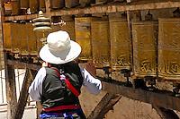 Tibetan Buddhist with hand-held prayer wheel circumambulates rows of prayer wheels on the Barkhor pilgrim circuit around the Jokhang Temple, Lhasa, Tibet.