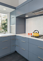 A contemporary kitchen with grey blue cabinets allowing plenty of storage. A textured splashback is set behind a gas hob.