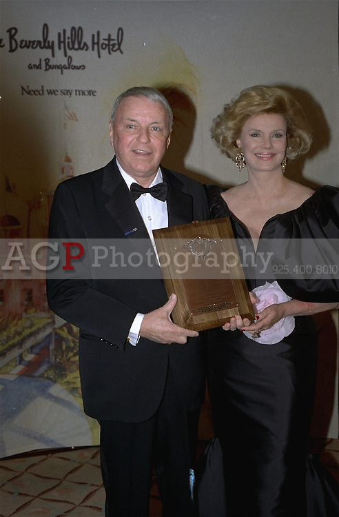 Jan 25, 1989 - Beverly Hills, California, USA - Entertainer Frank Sinatra with his wife Barbara on his side, proudly displays the Will Rogers Award presented him by the Beverly Hills Chamber of Commerce Wednesday January 25, 1989, at a star-studded event in Beverly Hills.  The award has been given annually for outstanding contributions to the world of entertainment.  Sinatra has been directly responsible for having raised more than $1 billion for worldwide charity..(Credit Image: © Alan Greth)