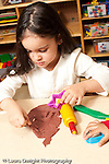 Education preschool 3-4 year olds art activity play dough girl cutting out shape of star in play dough vertical