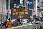 People pass in front of a sign advertising a COVID-19 vaccination center at the Jacob K. Javits Convention Center in New York, United States, on Saturday, January 16, 2021. Photograph by Michael Nagle