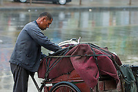 Man packing his tricycle under the storm, Datong, Shanxi, China.