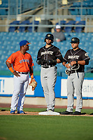 Charlotte Knights base runner Paulo Orlando (center), coach Guillermo Quiroz (right) talk with first baseman Dilson Herrera (left) during an International League game against the Syracuse Mets on June 11, 2019 at NBT Bank Stadium in Syracuse, New York.  Syracuse defeated Charlotte 15-8.  (Mike Janes/Four Seam Images)