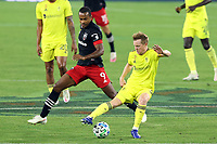 NASHVILLE, TN - SEPTEMBER 23: Dax McCarty #6 of Nashville SC tries to keep the ball away from Ola Kamara #9 of DC United during a game between D.C. United and Nashville SC at Nissan Stadium on September 23, 2020 in Nashville, Tennessee.