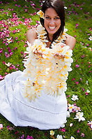 Beautiful Hawaiian woman showing off the fragrant plumeria leis she just made