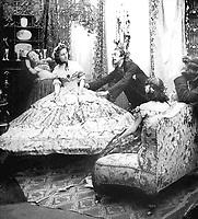 Femme essayant une robe a crinoline encombrante dans un salon vers 1860   --- Woman with a crinoline dress c. 1860