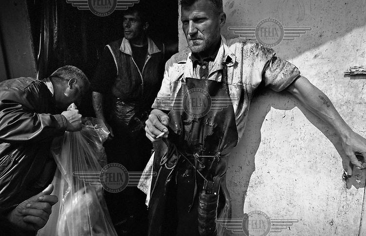 A lamb butcher and his collgeagues take a cigarette break in Sighetul Marmatiei, Maramures..