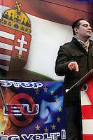 UNGARN, 14.01.2012. Budapest - II. Bezirk. Angesichts der Krise Ungarns fordert die rechtsextreme Jobbik-Partei den Austritt aus der EU und eine neue Ostorientierung des Landes. Demonstration vor der Vertretung der EU-Komisision in der Lövöház utca. Parteivorsitzender Gábor Vona vor ungarischer Flagge und Stop-EU-Poster: Es starrt der Ewige Jude. | In the ligth of Hungary's crisis the far right Jobbik party calls for leaving the EU. Demonstration close to the office of the EU commission in Lovohaz street. Party president Gabor Vona in front of the Hungarian flag and STOP-EU-poster: The Eternal Jew is looming..© Martin Fejer/EST&OST.