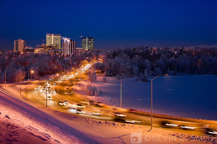 The Anchorage skyline at twilight with the lights from rush hour traffic on Minesota blvd. in the foreground, winter, Southcentral Alaska, USA.
