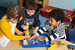 Education Preschool 3 year olds group of two boys and girl playing with sand in a plastic box