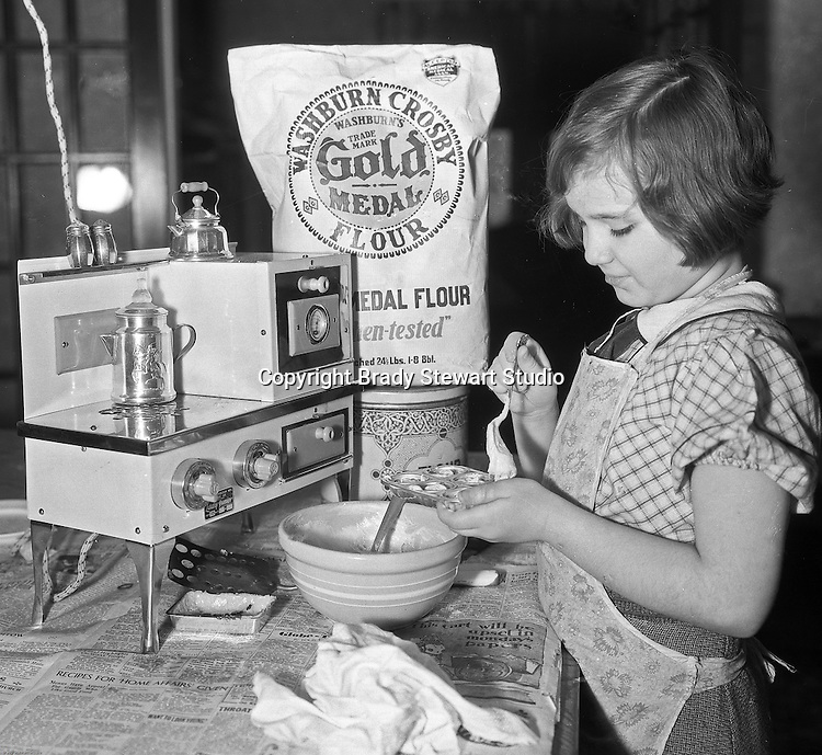 Product: Lady Junior Electric Stove<br /> Manufacturer:  Metropolitan Manufacturing Company (Chicago ILL)<br /> Product: Gold Medal Flour<br /> Manufacturer: Washburn Crosby (General Mills)<br /> <br /> Wilkinsburg PA:  Young girl baking cookies with a new electric oven and Gold Metal flour for a newspaper advertisement.  Brady Stewart was often contracted by local newspapers to photograph products for newspaper advertisements