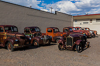 Waiting to be restored, antique truckes for sale line a lot on mainstreet in a rural Colorado town.