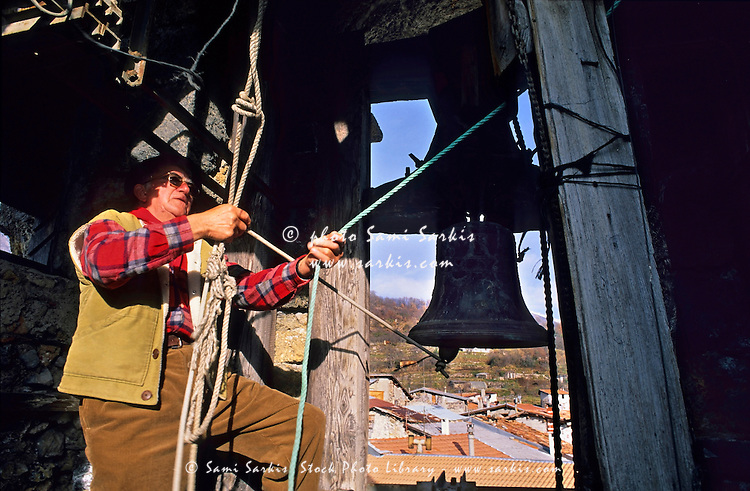 Man ringing the bells inside a church bell tower in Belvédère, French Alps, France.