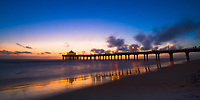 Sunset on the lit-up Manhattan Beach pier and Roundhouse Aquarium silhouettes, reflecting on Pacific Ocean and wet sand, Los Angeles California USA