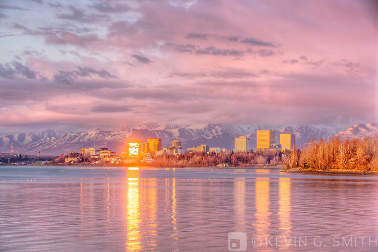 Sunset light falls on the downtown Anchorage Skyline and is reflected in the waters of Knik Arm during high tide, Spring, Southcentral Alaska, USA.