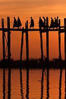 Myanmar, Burma, Mandalay, Amarapura.  Burmese Monks Walking Home over the U Bein Bridge at the end of the day.  The teak footbridge is 200 years old, and 1300 yards long.